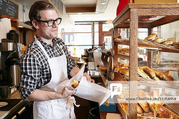 Männlicher Arbeiter in Bäckerei  der Backwaren für einen Kunden in eine Papiertüte steckt