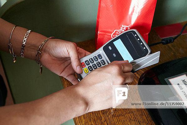 Kunde in Bäckerei beim Bezahlen von Waren  mit Kartenautomat  Nahaufnahme