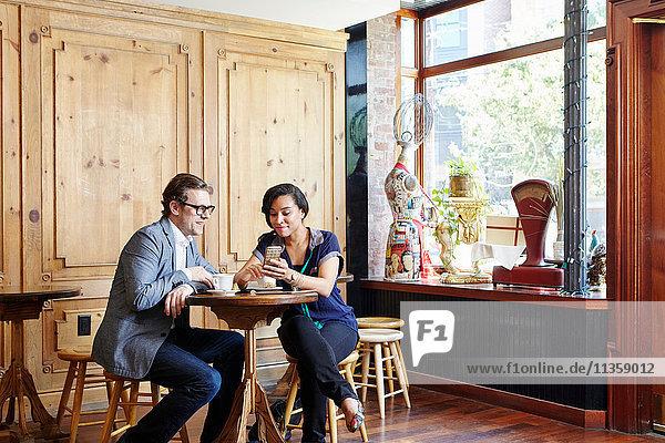 Mann und Frau sitzen in einem Café  trinken Kaffee und schauen auf ein Smartphone