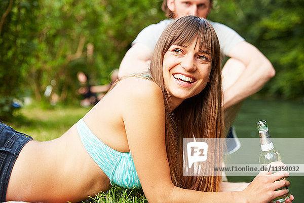 Paar entspannt sich im Park  junge Frau hält Glasflasche