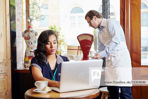 Junge Frau sitzt im Café und benutzt einen Laptop
