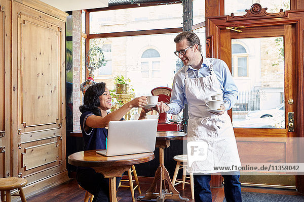 Junge Frau sitzt im Café  benutzt Laptop  männlicher Arbeiter nimmt leere Kaffeetasse