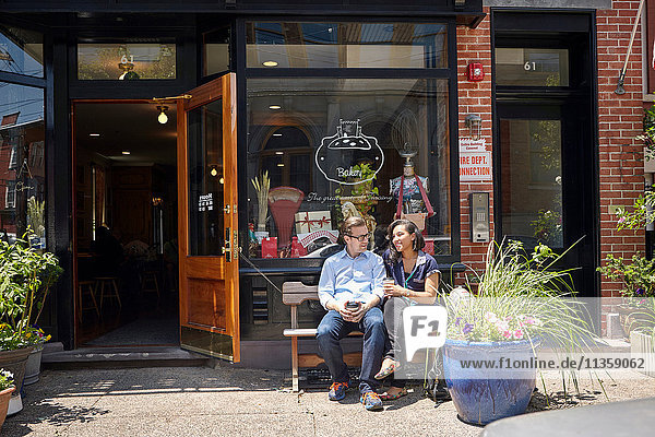Couple sitting on bench  outside bakery  holding coffee cups