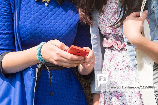 Zwei Frauen  die ein Smartphone benutzen  mittlerer Abschnitt