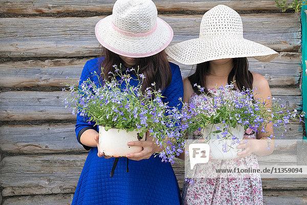 Zwei Frauen tragen Sonnenhüte  halten Topfpflanzen  Gesichter versteckt