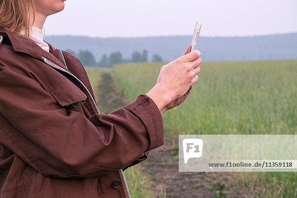 Frau steht im Feld und fotografiert mit einem Smartphone  Mittelteil  Ural  Russland