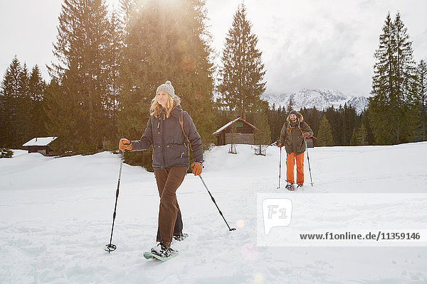 Couple snowshoeing across snowy landscape  Elmau  Bavaria  Germany