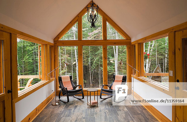 Lesesaal mit Keramikfliesenboden und zwei schwarzen Lederschaukelstühlen in Blockhütte im Landhausstil  Quebec  Kanada
