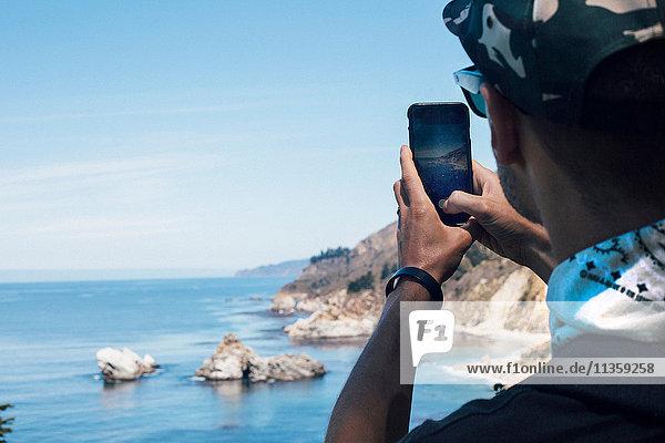 Über-Schulter-Ansicht eines Mannes  der die Küste auf einem Smartphone fotografiert  Big Sur  Kalifornien  USA