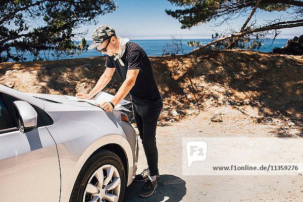 Man on road trip reading map on car hood  Big Sur  California  USA