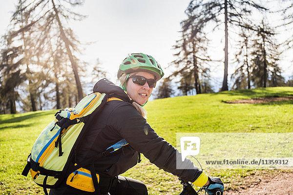 Mittlere erwachsene Frau auf dem Fahrrad  die in die Kamera schaut  Jenesien  Südtirol  Italien
