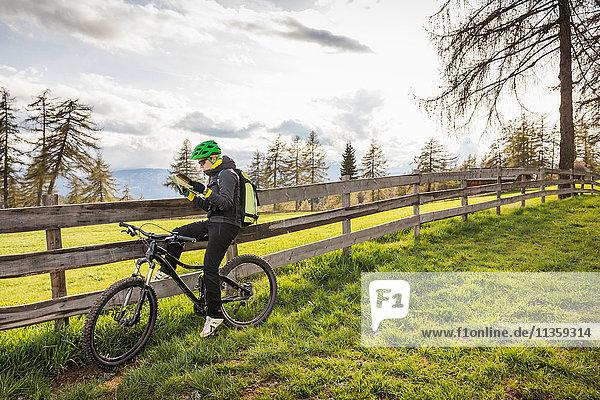 Frau auf Fahrrad Lesekarte  Jenesien  Südtirol  Italien