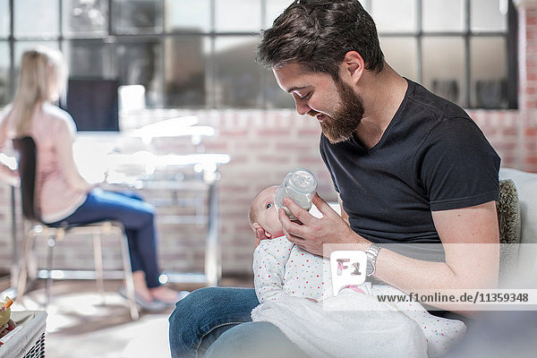 Father sitting  feeding baby daughter  mother sitting at desk  working  behind