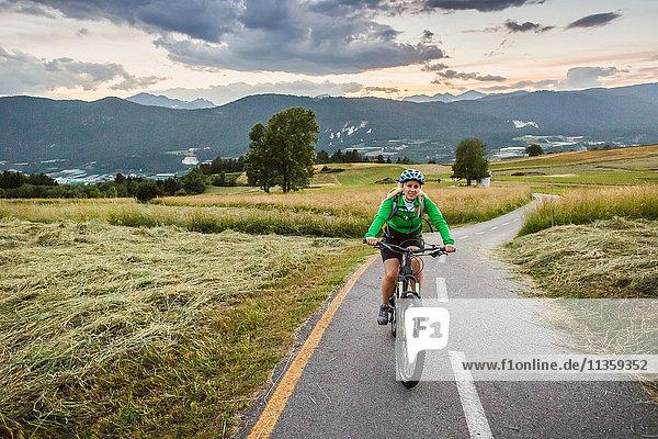 Frau radelt auf der Strasse  Fondo  Trentino  Italien