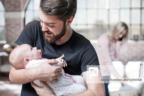 Vater hält Tochter im Arm  Mutter nimmt Telefonanruf im Hintergrund entgegen