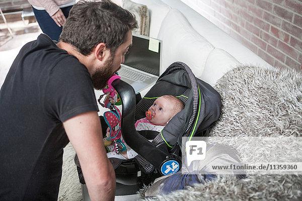 Vater verzieht Gesicht bei Baby-Tochter im Autositz
