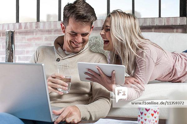 Paar zu Hause  Mann mit Laptop  Frau mit digitalem Tablet  lachend