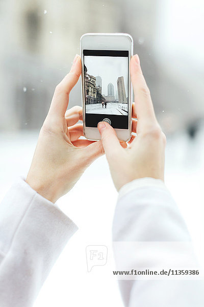 Young woman using smartphone to photograph the Christian Science Centre and Prudential building with snow  Boston  Massachusetts  USA
