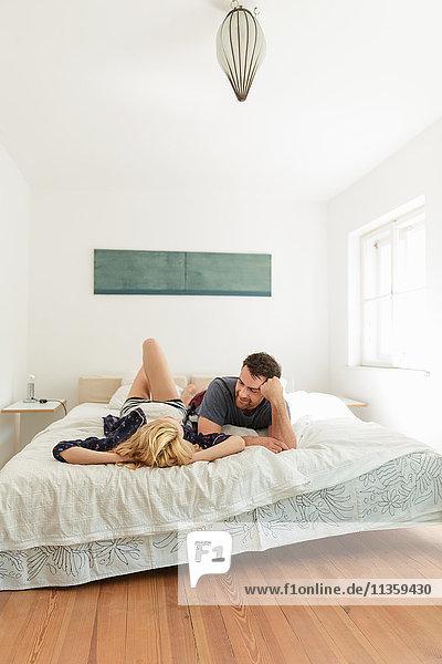 Paar  das auf dem Bett liegt und spricht