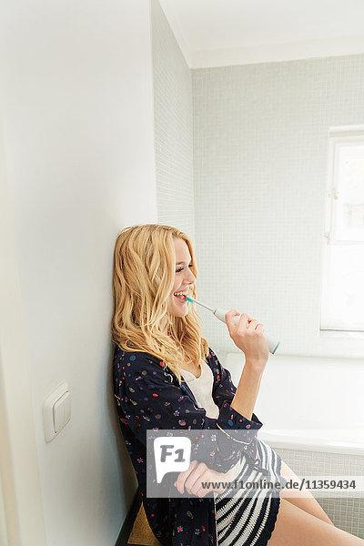 Frau im Badezimmer beim Zähneputzen lächelnd