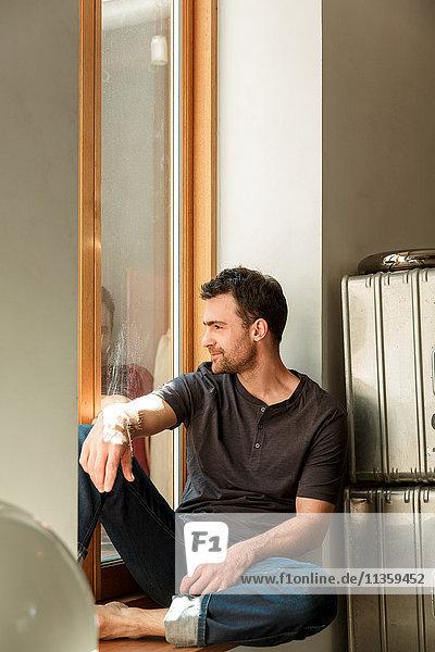 Mann sitzt und schaut aus dem Fenster
