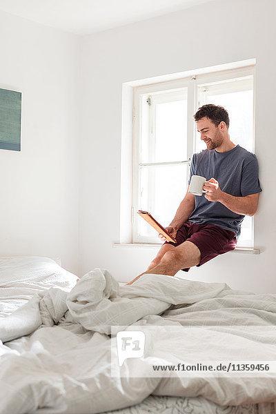 Mann hält Becher mit digitalem Tablett