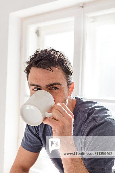 Mann trinkt aus Becher