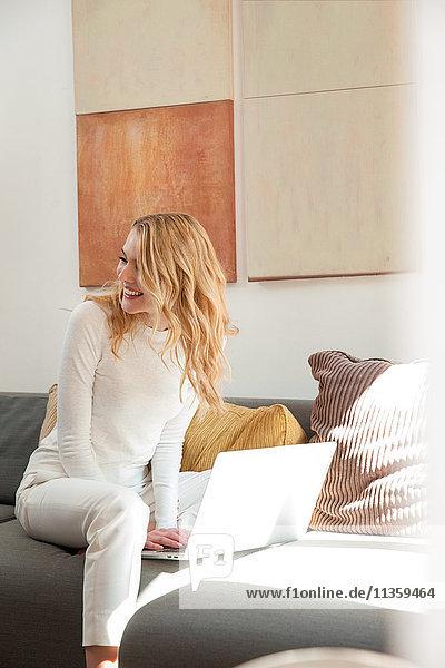 Frau auf dem Sofa mit Laptop schaut lächelnd weg
