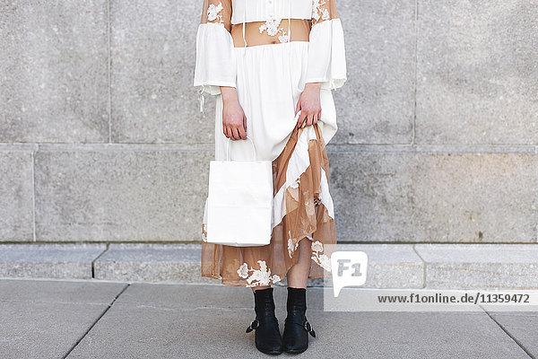 Niedriger Abschnitt einer Frau mit Einkaufstasche