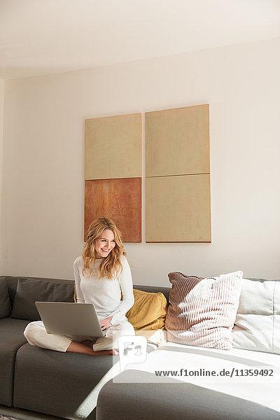 Frau auf Sofa mit Laptop lächelt