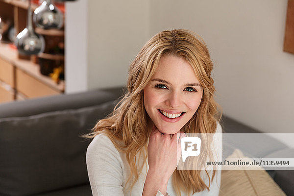 Portrait of blonde woman hand on chin looking at camera smiling