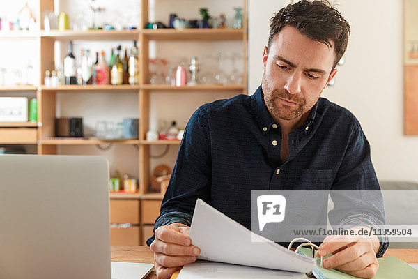 Mann mit Laptop sieht sich Papierkram an