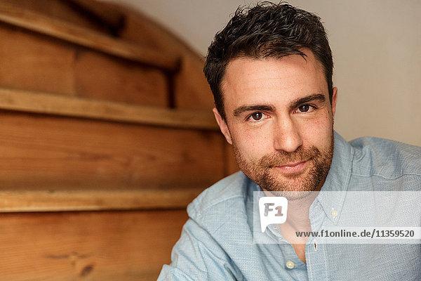 Porträt eines Mannes mit Bartstoppeln auf einer Treppe  der in die Kamera schaut