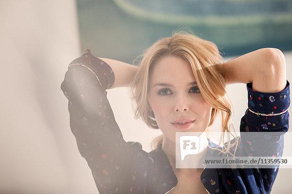 Porträt einer blondhaarigen Frau Hände hinter dem Kopf wegblickend