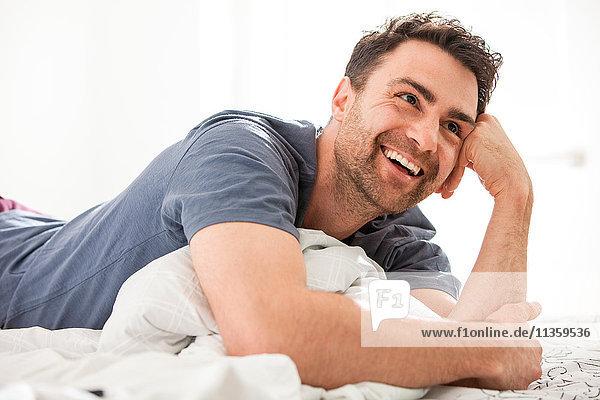 Mann liegt auf dem Bett  ruht auf dem Ellbogen und schaut lächelnd weg