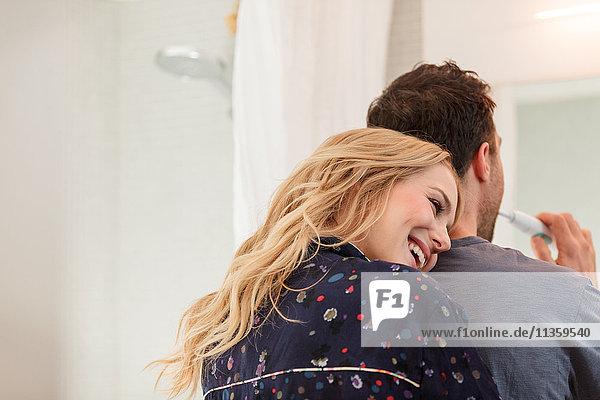Paar im Badezimmer beim Zähneputzen umarmen