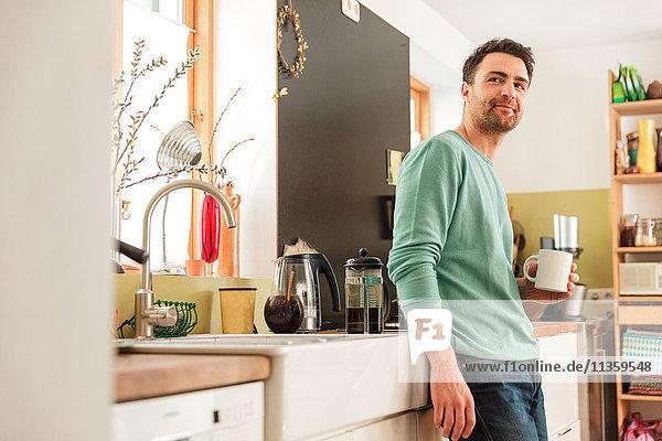 Mann in der Küche hält Kaffeetasse und schaut lächelnd in die Kamera
