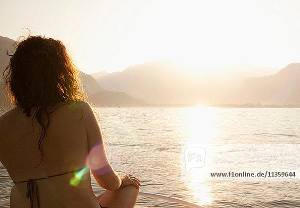 Rückansicht einer Frau  die den Sonnenuntergang betrachtet  Capo Testa  Gallura  Sardinien  Italien