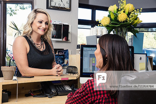 Receptionist attending to customer in hair salon