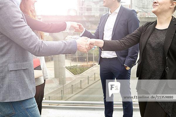 Neck down view Geschäftsfrauen und Männer beim Händeschütteln auf der Fußgängerbrücke  London  UK