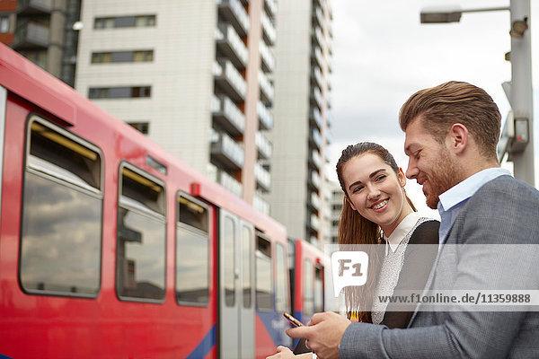 Geschäftsmann und Frau beim Lesen von Smartphone-Texten auf dem Bahnsteig  London  UK