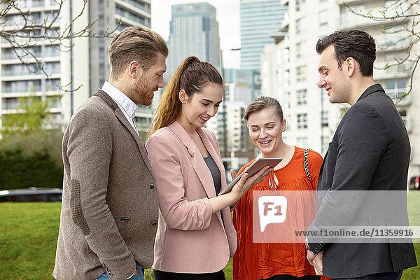Businesswomen and businessmen looking at digital tablet outside office  London  UK