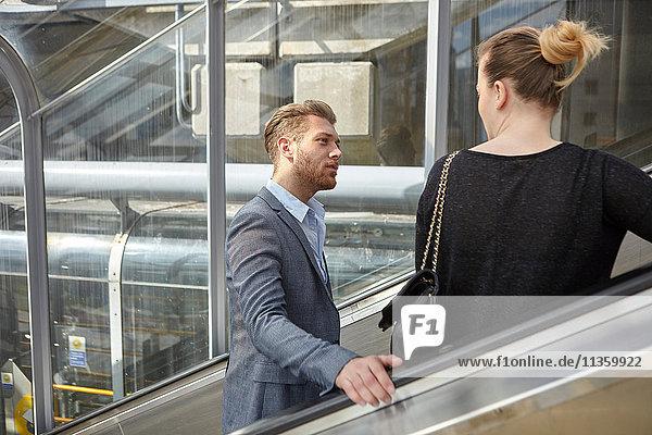 Geschäftsmann und Frau im Gespräch auf der Rolltreppe  London  UK