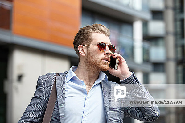 Young businessman wearing sunglasses talking on smartphone outside office  London  UK