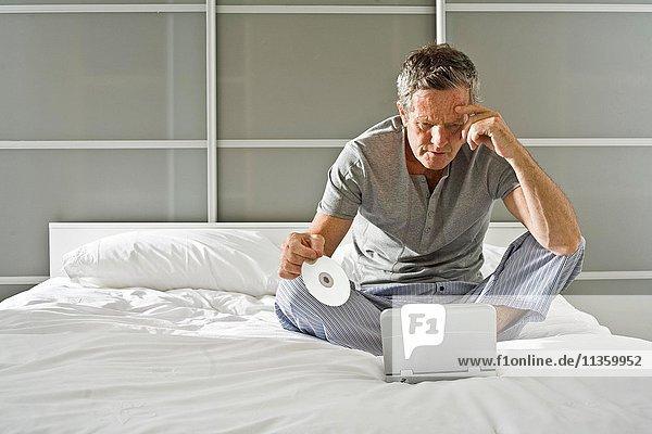 Älterer Mann sitzend  CD haltend und auf den Laptop starrend