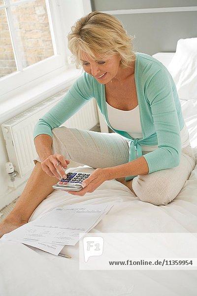 Reife Frau auf dem Bett sitzend mit Taschenrechner