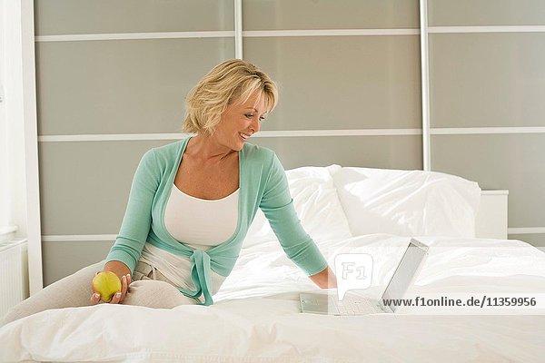 Reife Frau,  die auf dem Bett sitzt und auf dem Laptop surft