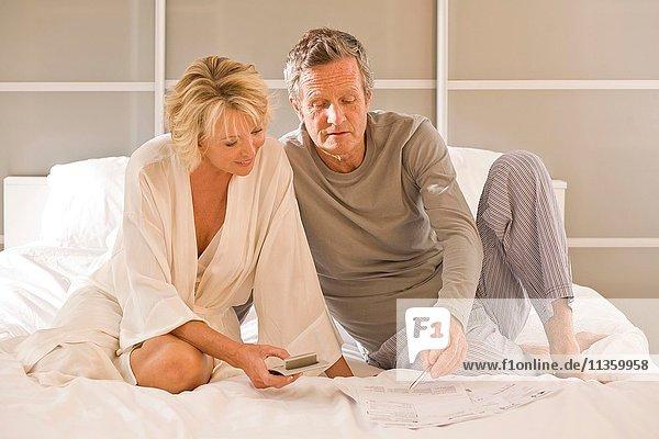 Paar auf dem Bett sitzend mit Taschenrechner