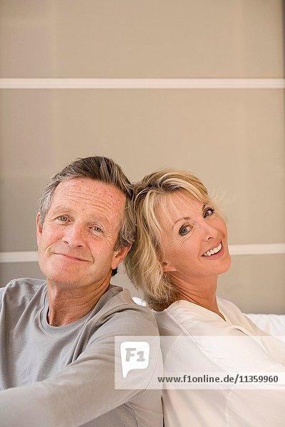 Porträt des glücklichen Paares Rücken an Rücken auf dem Bett