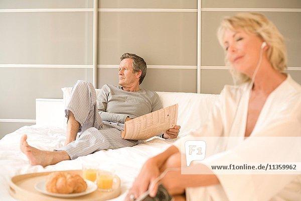 Entspannen auf dem Bett  Zeitung lesen und Kopfhörer hören